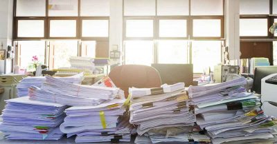 Paper records piling up on a desk to be filed using a records retention policy