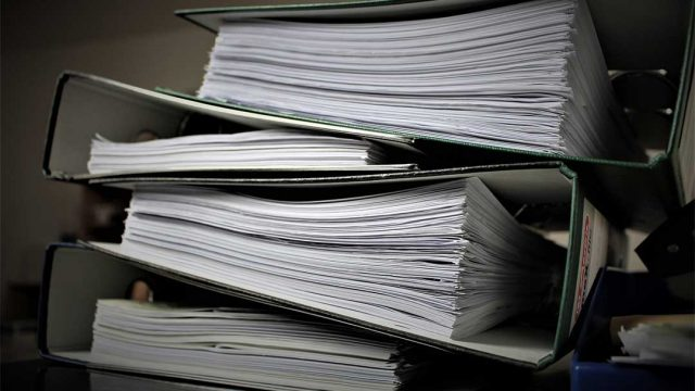 Large binders of paper storing government agency documents and information.