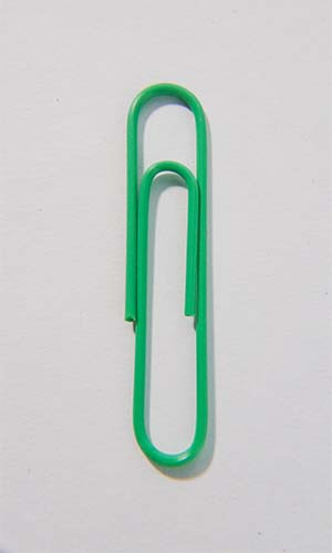 Green paper clip removed from a pages in a document scanning project.